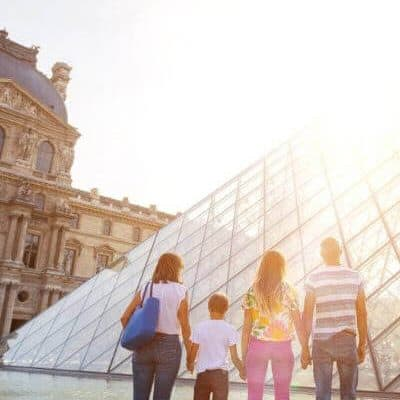 Family Looking at the Glass Pyramid of the Louvre Museum