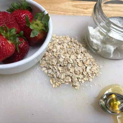 Ingredients for DIY Oatmeal mask bowl of fresh strawberries, bunch of oats, clear jar with plain yogurt and spoon, and spoon filled with honey all on a white cutting board