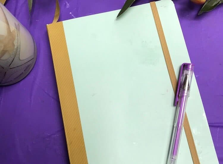 Bullet Journal on Purple Background with Purple Pen on Top
