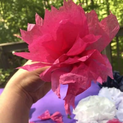 Pink Easy Paper Flower Held Up by Hand with Trees in the Background
