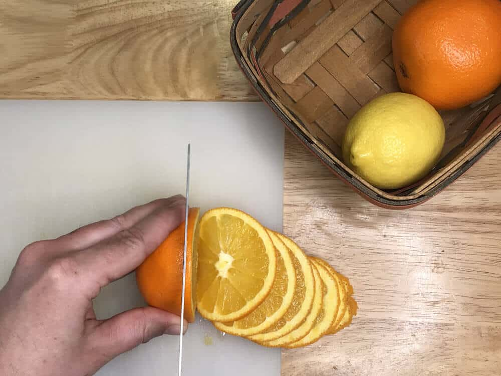 Hand holding orange and cutting orange slices with a knife on white cutting board