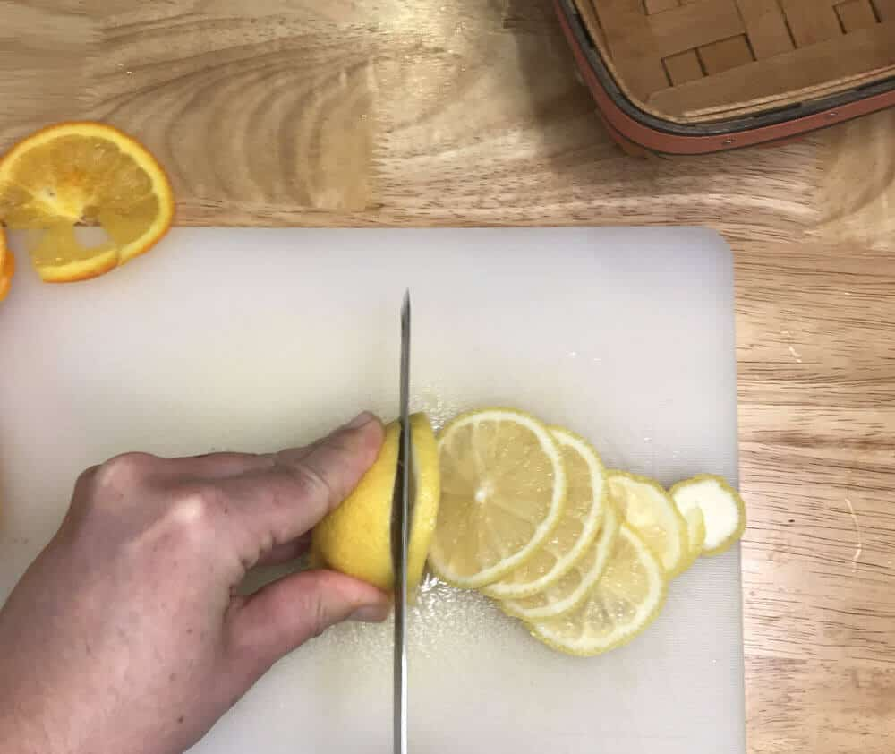 hand lemon and cutting lemon into slices with knife on white cutting board