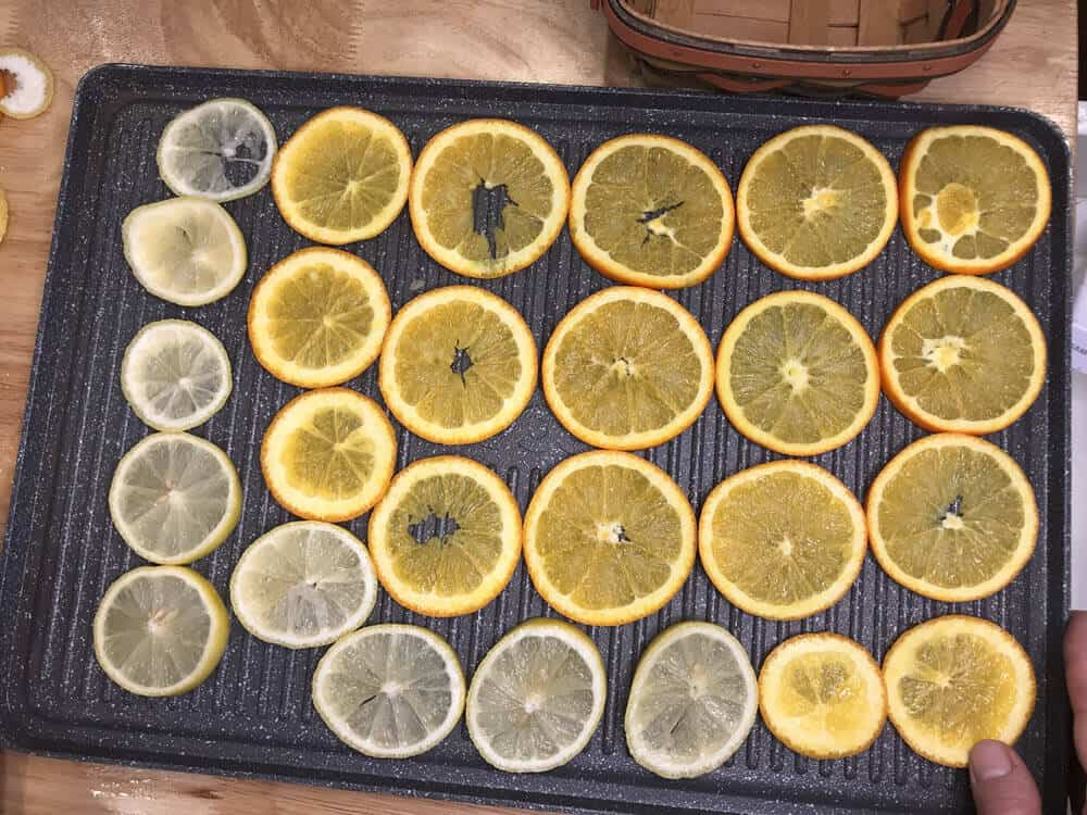 orange and lemon slices placed on grilling tray for dried orange garland