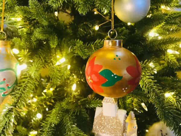 hand painted christmas ornament hanging on a tree lit with white lights