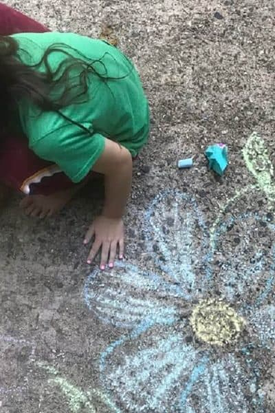 fun stay at home kid activities - little girl drawing flowers on the driveway with sidewalk chalk